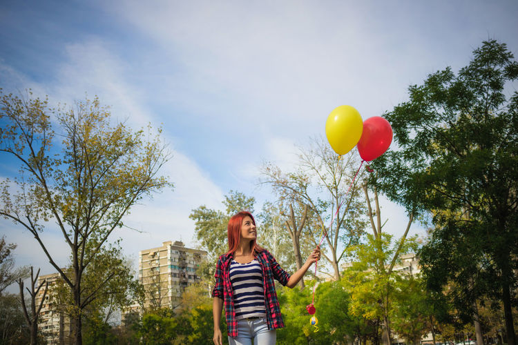 Low angle view of smiling woman with balloons standing against sky in park