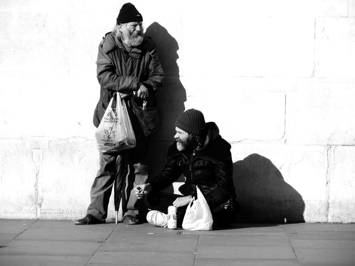 Senior Beggars On Street Against Wall During Sunny Day