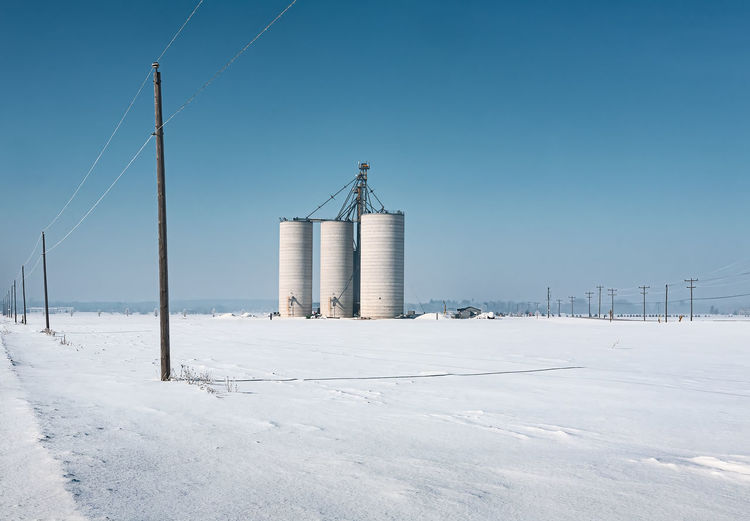 Three agriculural silos photographed on a snow covered open field on a cold winter's day.