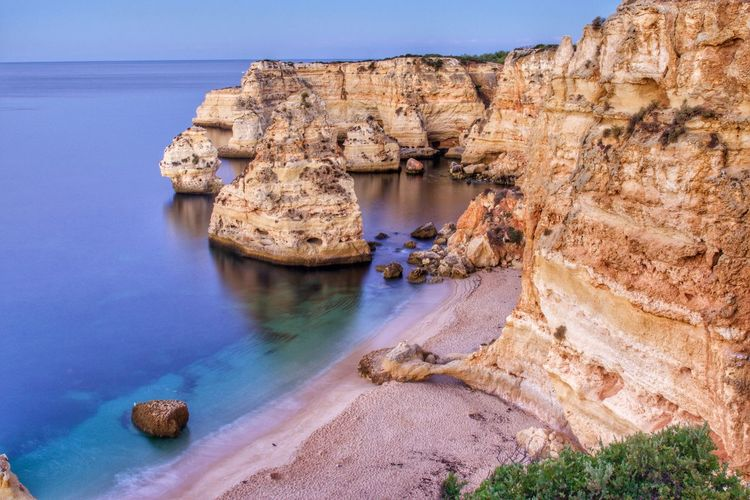 Scenic view of rock formations by sea at praia da marinha