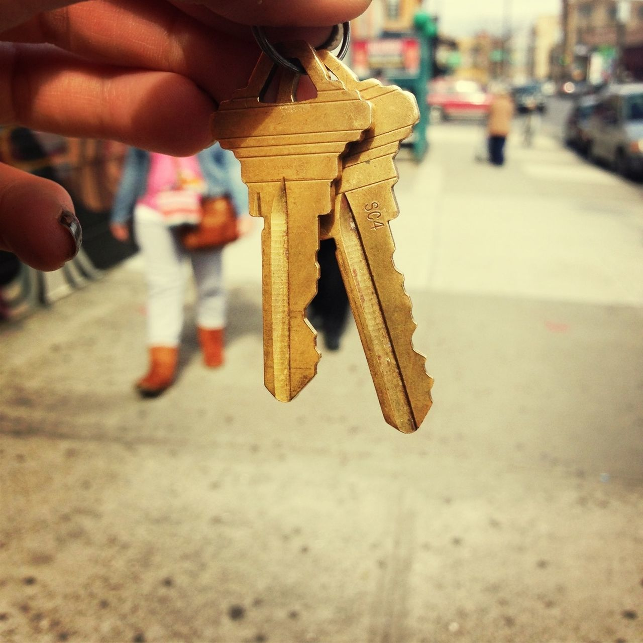 Close-up of cropped hand holding keys on street