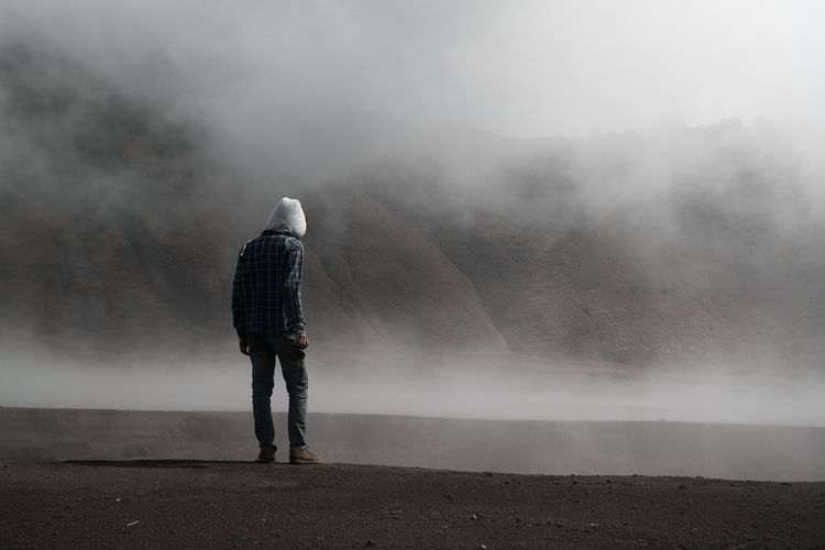 Rear view of man standing on mountain during foggy weather