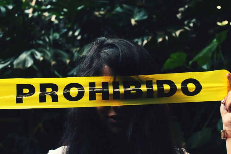 Close-Up Of Woman Holding Yellow Tape With Text