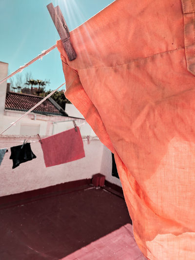 colorful laundry Rooftop SPAIN Coral Colored Orange Color Turquoise Colored Sunny Sunrays Lensflare Red Clothesline Drying Fabric Textile Cloth Hanging Clothespin Clothes Laundry Settlement Building Residential Structure