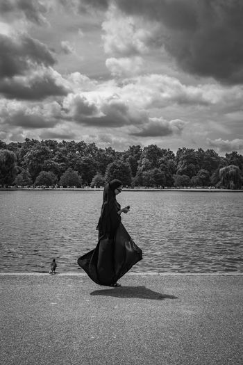 Rear view of woman sitting on lake against sky