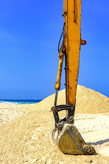Yellow excavator over sand at beach in a sunny day Buldozer Dozer Heavy Industry Machine Machinery Tractor Transportation Work Beach Blue Clear Sky Day Earthmover Equipment Escavator Gear Industry Machinery Metal Metallic Outdoors Sand Sky Sunlight