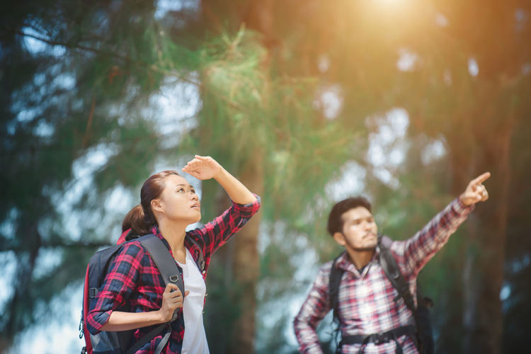 Woman Shielding Eyes While Male Hiker Showing Something In Forest