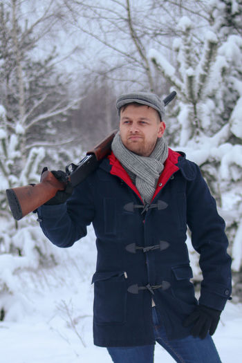 Young man holding rifle while standing outdoors during winter