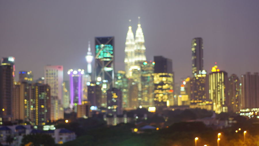 Malaysia city skyline illuminated at night.Blurry photo light and bokeh. Architecture Building Building Exterior Built Structure City Cityscape Financial District  Illuminated Landscape Modern Nature Night Nightlife No People Office Office Building Exterior Outdoors Sky Skyscraper Tall - High Tower Travel Destinations Urban Skyline