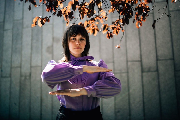 Portrait of girl standing against purple outdoors