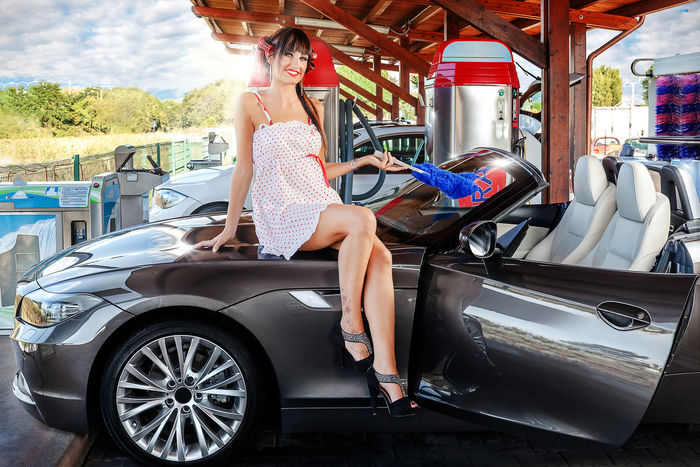 A girl in her nightgown and curlers, laying on a car in the drying department of a car wash. Beatiful Girl Beautiful Woman Car Carwash Carwashing Curles Day Land Vehicle Leisure Activity Lifestyles Mode Of Transport Nightgown One Person Outdoors People Real People Sitting Stationary Transportation Young Adult Young Girl Young Women