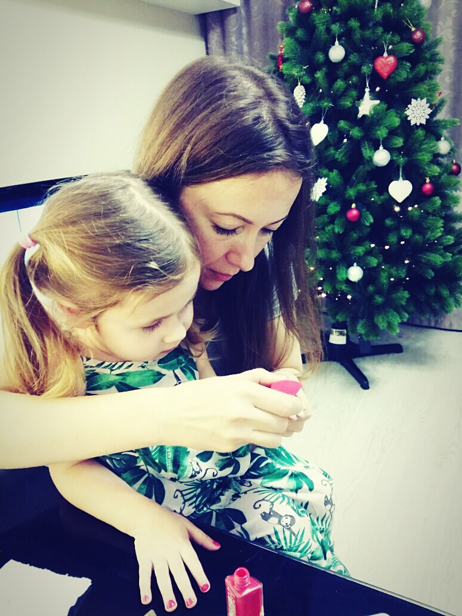 child, females, family, real people, family with one child, love, girls, lifestyles, tree, embracing, childhood, christmas, parent, home interior, happiness, christmas tree, indoors, adult, cheerful, smiling, holiday - event, women, people, togetherness, domestic room, christmas ornament, christmas decoration, domestic life, young adult