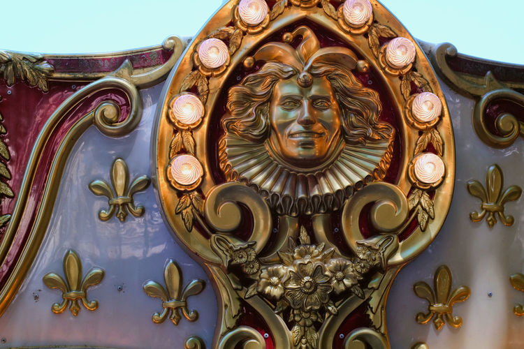Detail on antique decoration of a carousel Carousel Ornate Gold Colored Day Close-up No People Gold Outdoors Sky Lamps Light Bulbs Joker Decoration Fleur De Lys Gold White Red Royalty Royal California Jacks Jack Santa Rosa USA