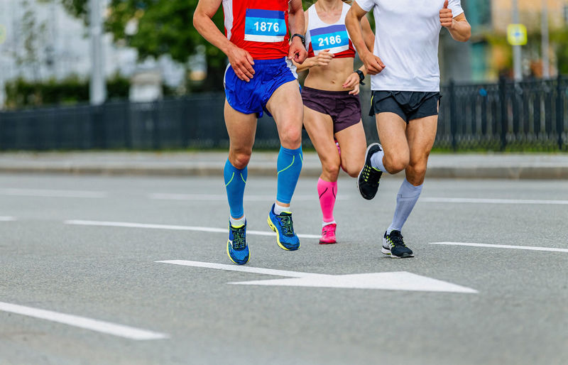 Two male and one female athletes in compression socks run city marathon