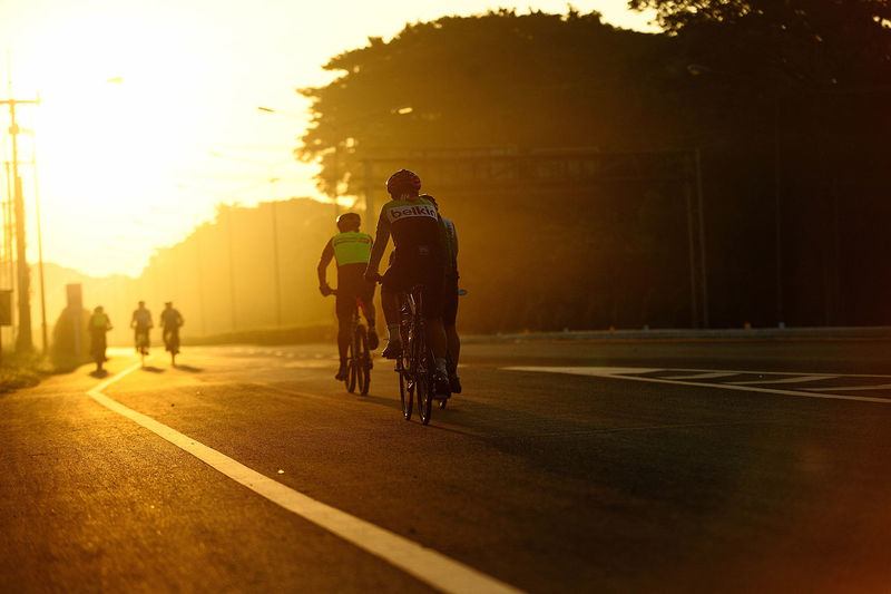 People riding bicycle on road against sky
