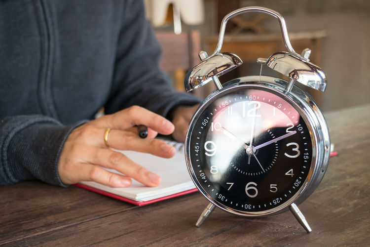Close-up of man writing in book with alarm clock on table