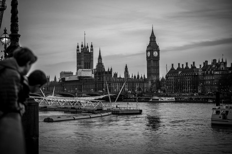 People by thames river against big ben in city