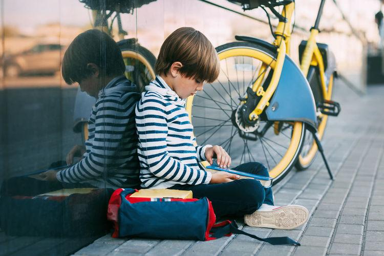 Boys sitting on sidewalk