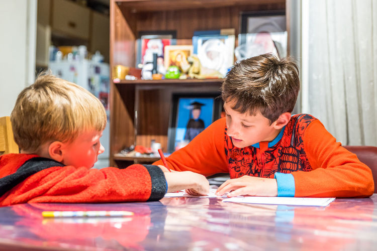 Children writing on table