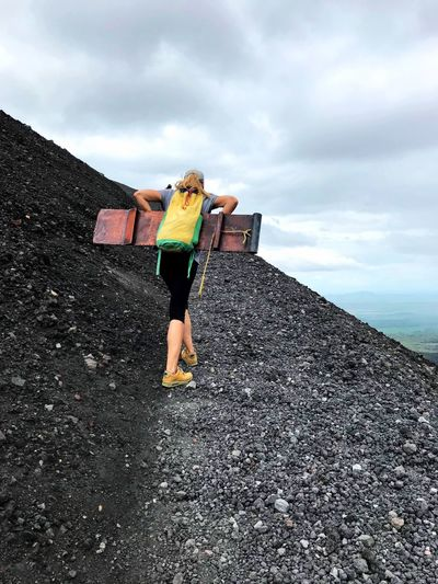 Woman carrying plank and backpack while climbing mountain against sky
