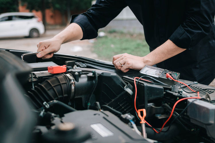 Midsection of man repairing car engine on roadside
