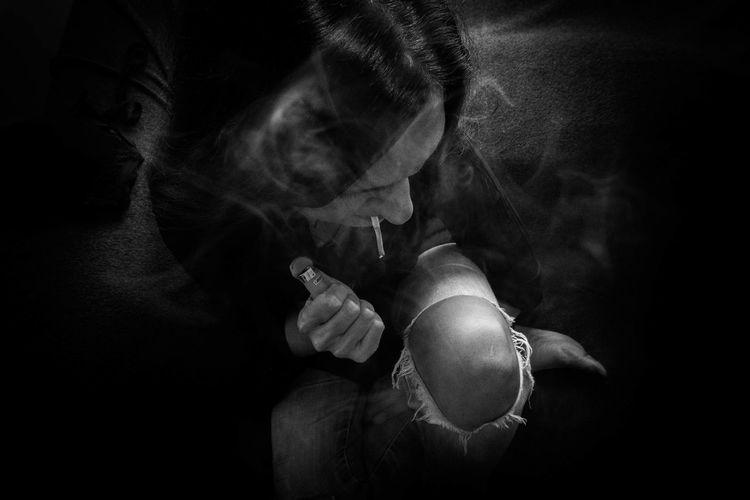 High angle view of woman smoking marijuana joint in darkroom