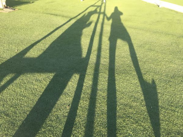 Shadows of person sitting on swing and person next to it with foot in air. Waysofseeing Foot Silhouette Day Focus On Shadow Golf Golf Club Golf Course Golfer Grass Green Color Leisure Activity Lifestyles Long Shadow - Shadow Men Nature Outdoors People Real People Shadow Standing Sunlight Swing Togetherness Two Two People