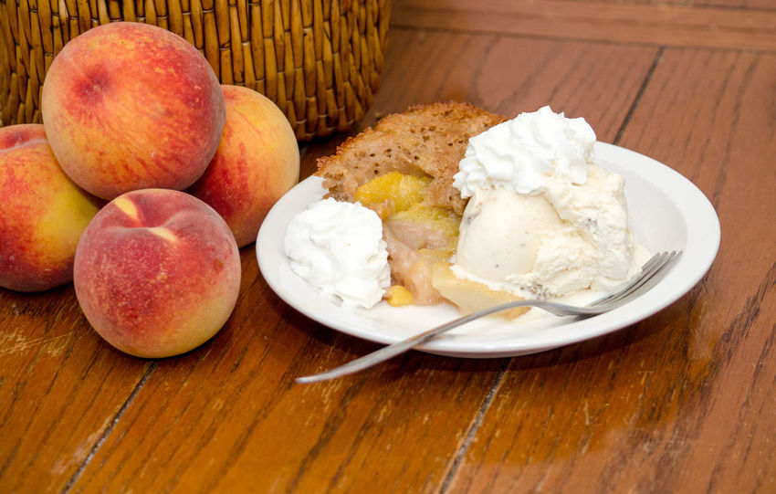 pile of fresh peaches next to home made peach cobbler Agriculture Fresh Produce Hello World Nature Orange Summertime USA Vitamins Dessert Food Fresh Fruit Healthy Eating Juicy Just Picked Michigan Peaches Natura' Organic Peach Peach Cobbler Peaches Produce Sweet Tasty Yellow