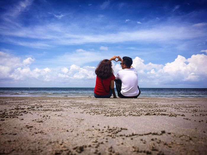 Couple Making Heart Shape With Hands While Sitting At Shore Against Cloudy Sky