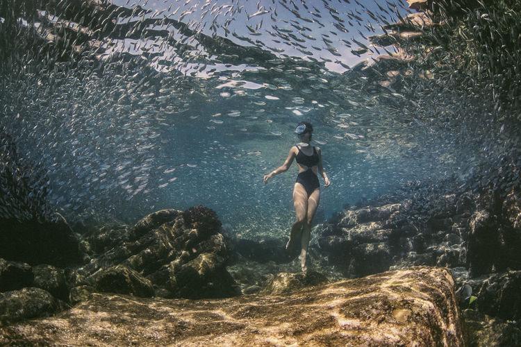 Woman wearing bikini swimming in sea