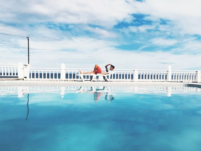 Mid Distance View Of Man Lying At Poolside Against Cloudy Sky