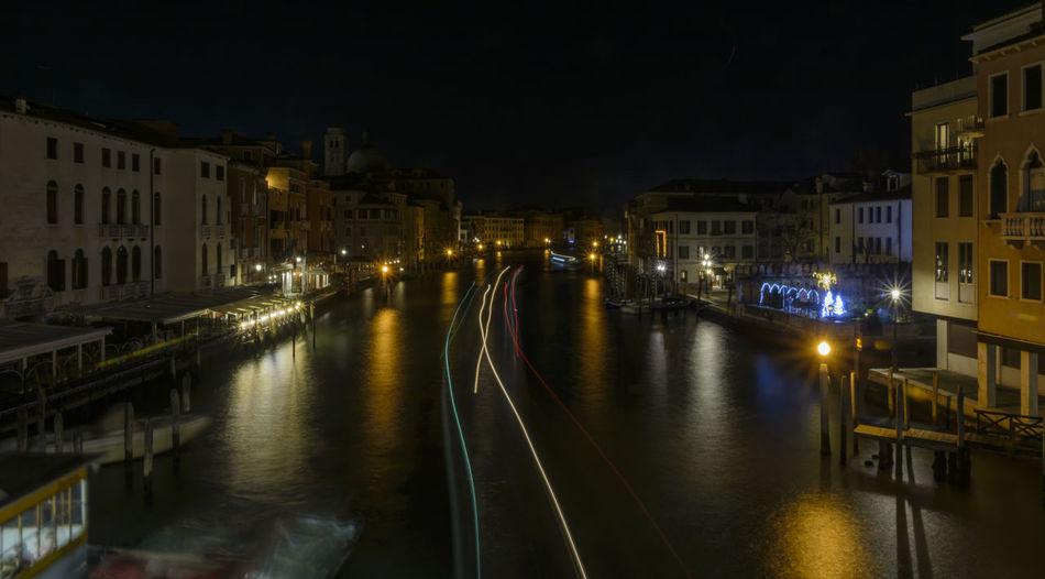 Canal amidst illuminated city against sky at night