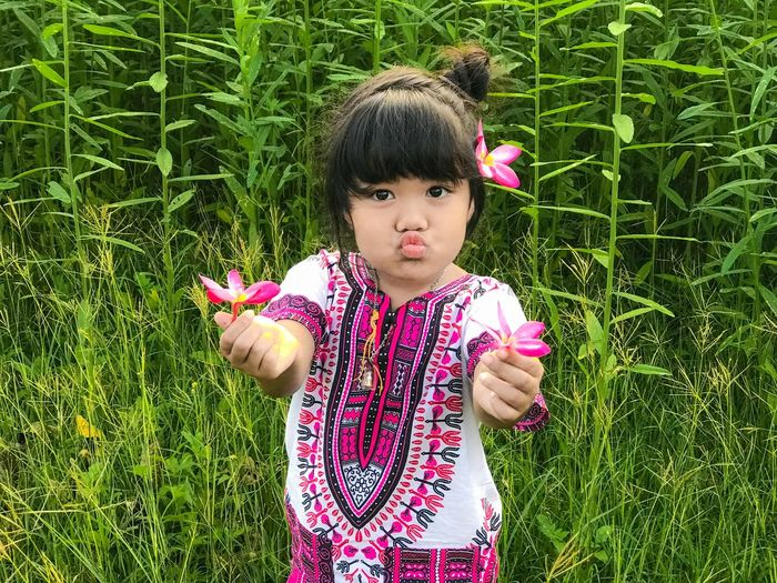 Portrait Of Cute Girl Holding Pink Flowers On Field