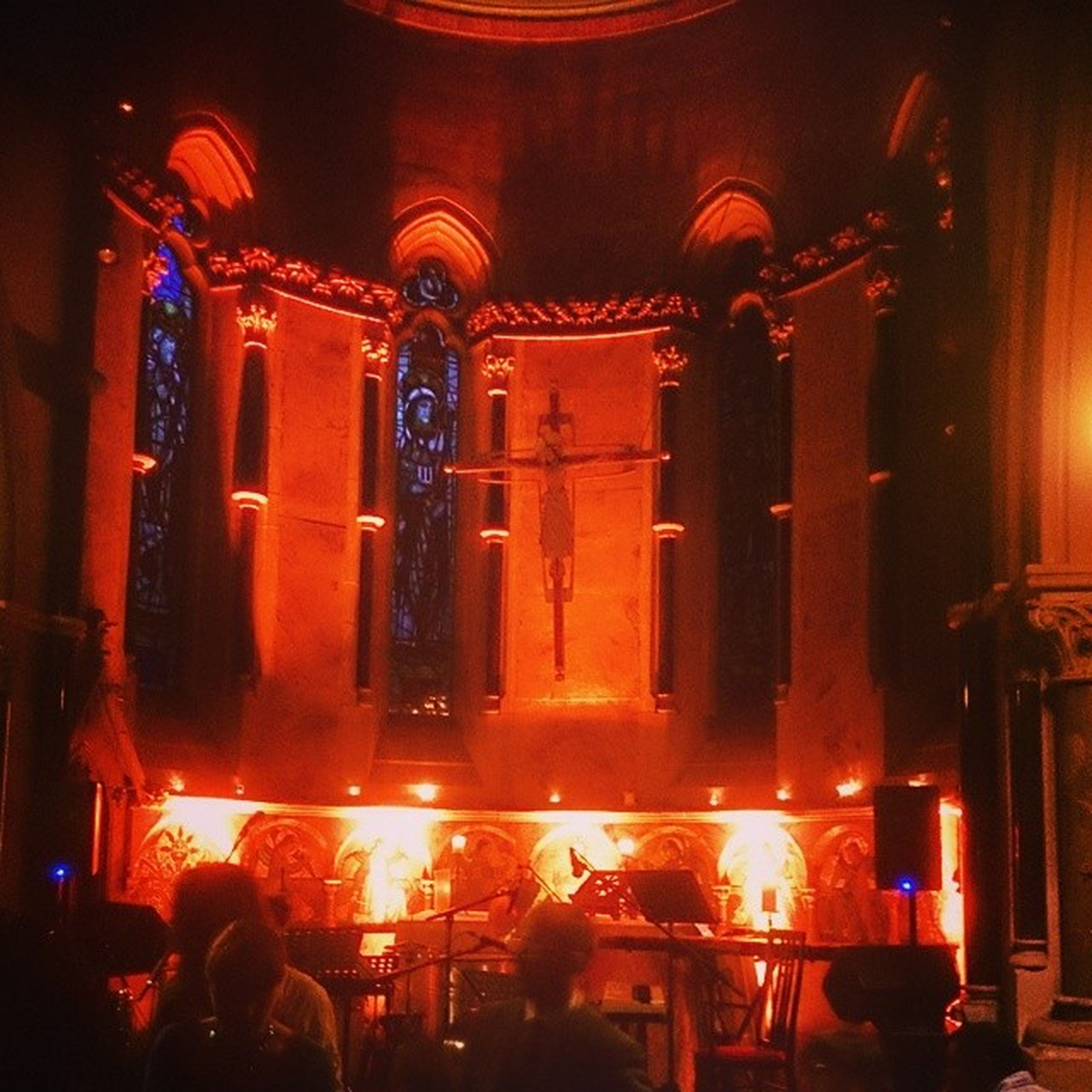 illuminated, indoors, night, lighting equipment, men, large group of people, light - natural phenomenon, arts culture and entertainment, built structure, architecture, lifestyles, person, dark, glowing, leisure activity, religion, church, place of worship, spirituality