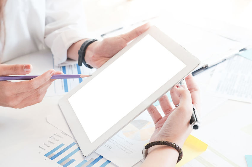 Business people Consulting and business planning. Blank Business Communication Computer Connection Digital Tablet Finger Hand Holding Human Body Part Human Hand Indoors  Men Occupation One Person Paper Real People Table Technology Wireless Technology Working
