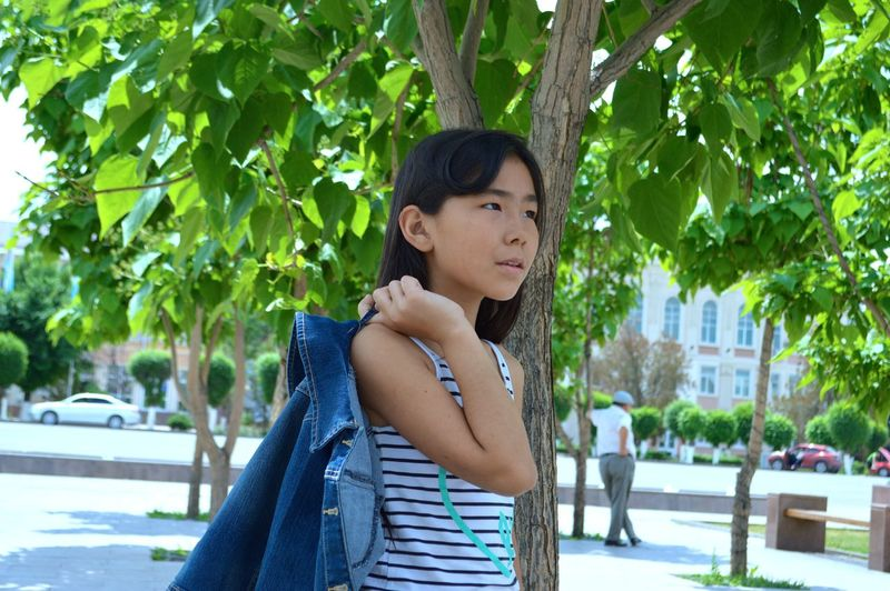 Girl Carrying Denim Jacket While Standing By Tree