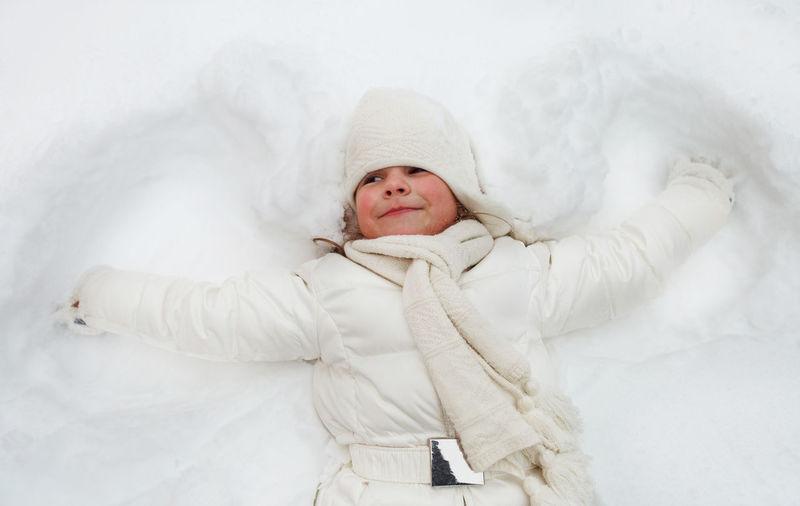 Full length of cute baby girl lying in snow
