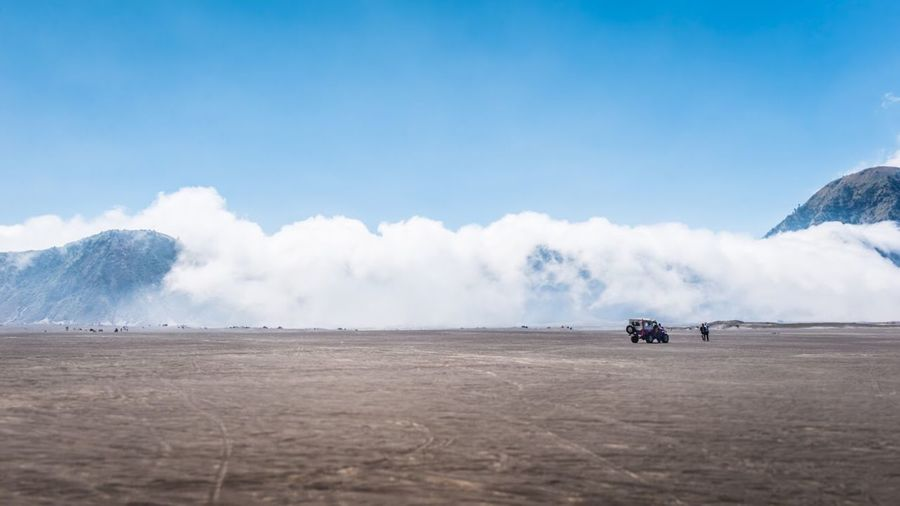 The car on land against sky, picture of a jeep car parked far away in the mountains and clouds.