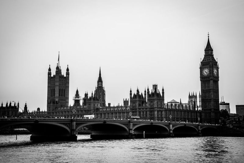 Westminster bridge and big ben by thames river against sky in city