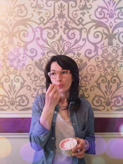 Portrait of mid adult woman eating ice cream against patterned wall at home