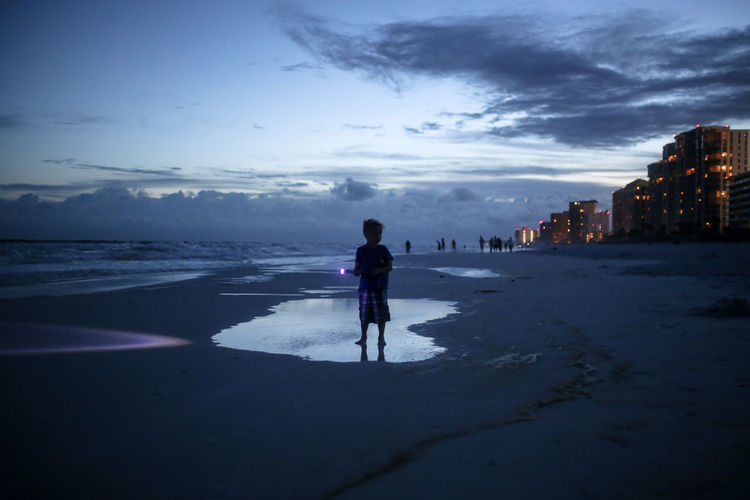 Full length of boy holding flashlight while standing at beach against sky