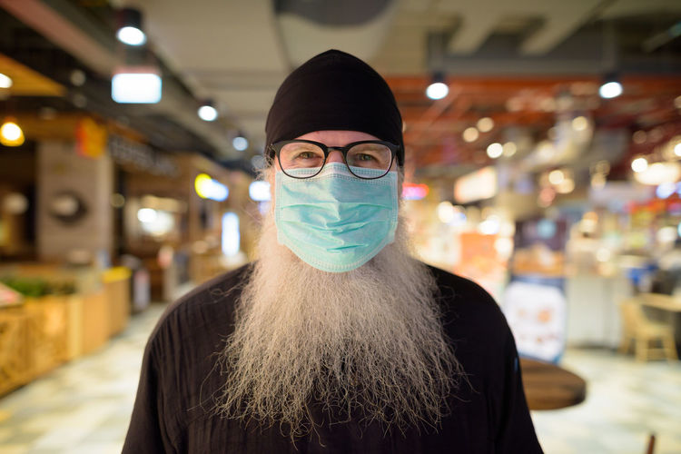 Portrait of man wearing mask standing at shopping mall