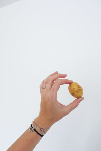 Midsection of person holding apple against white background
