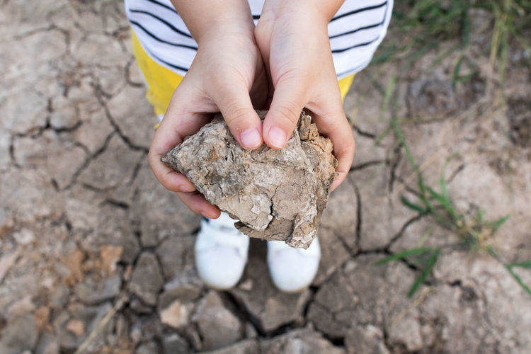 Low section of kid holding stone