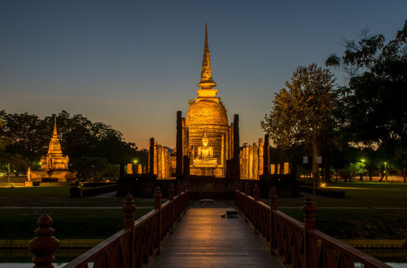 Ancient temples in sukhothai Buddha Buddhist Temple Thailand Built Structure Architecture Belief Religion Tree Place Of Worship Building Spirituality Sky Building Exterior Plant Nature Direction The Way Forward Illuminated Dusk The Past History Outdoors Spire