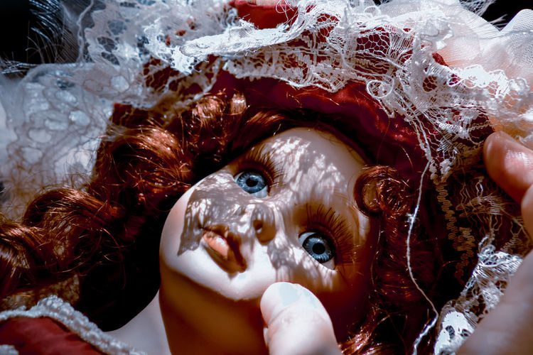 Close-up portrait of doll face with red hair
