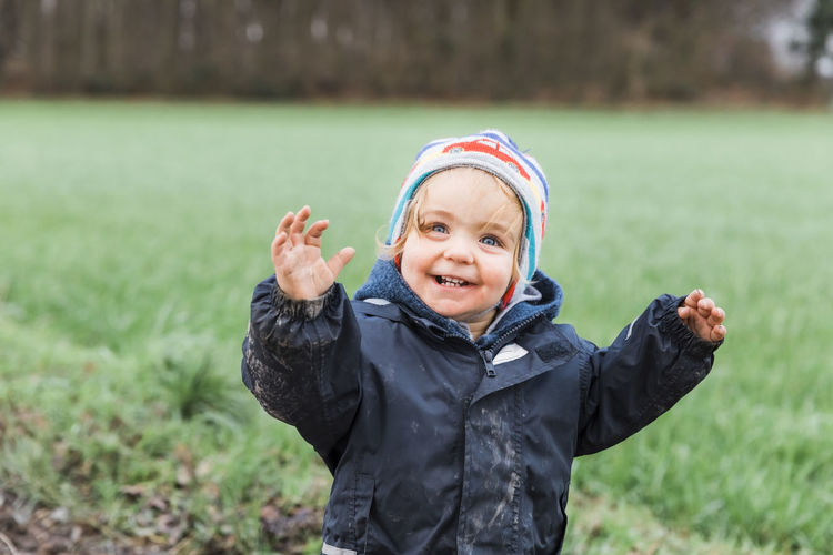 Happy toddler girl in front of field - Kempen, Germany Arm Arms Raised Baby Beautiful Beauty Blue Eyes Carefree Casual Caucasian Cheerful Cheering Child Childhood Close-up Confidence  Cute Emotion Expression Face Field Forest Front View Fun Girl Grass Hand Happy Headshot Innocence Jacket Joy Knit Hat Laughing Looking At Camera Nature One Outdoors People Portrait Positive Smiling Standing Success Teeth Toddler  Tree Waist Up Watching Winter Woods One Person Day Focus On Foreground Real People Warm Clothing The Portraitist - 2019 EyeEm Awards