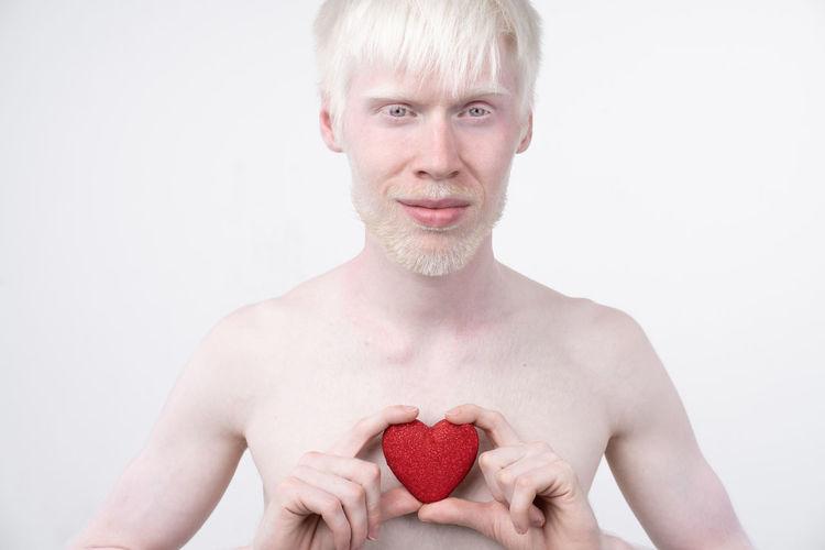 Portrait of shirtless man holding heart shape against white background