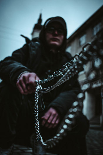 Full length of young man holding chain crouching on street