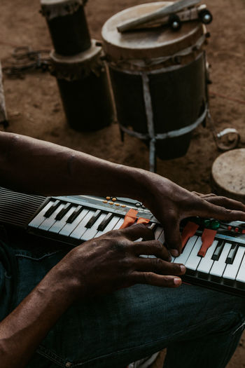 Midsection of man playing piano while sitting outdoors